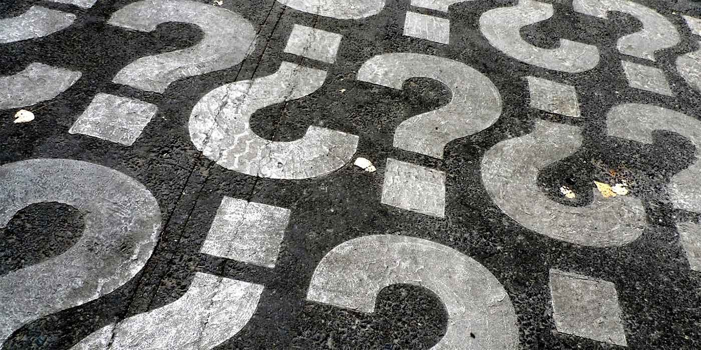 photo of question marks on tarmac