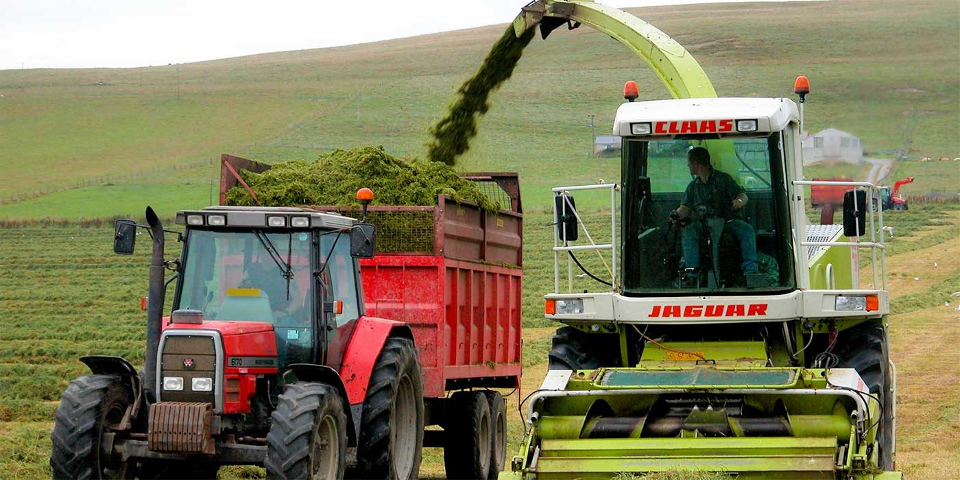 Photo of a tractor and combine collecting silage