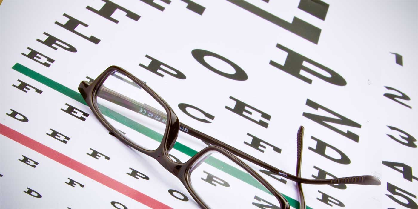 Photo of glasses and an eye chart