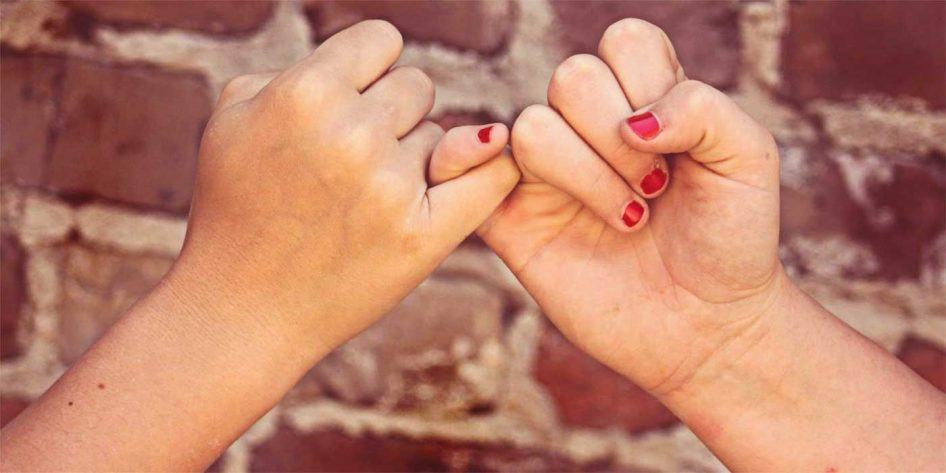 Photo of two hands grabbing fingers to make a pinky promise