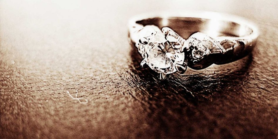 Photo of an engagement ring sitting on leather