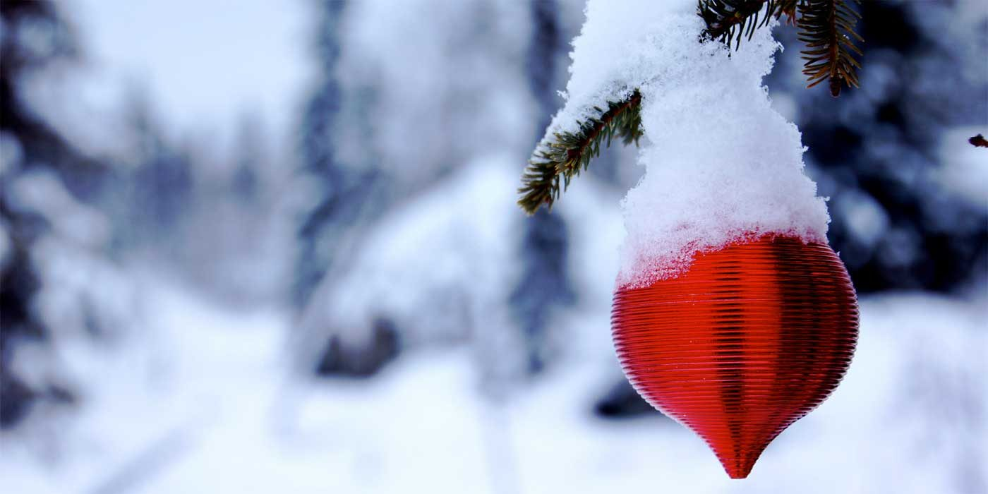 Photo of a bauble hanging on an outdoor Christmas tree in the snow