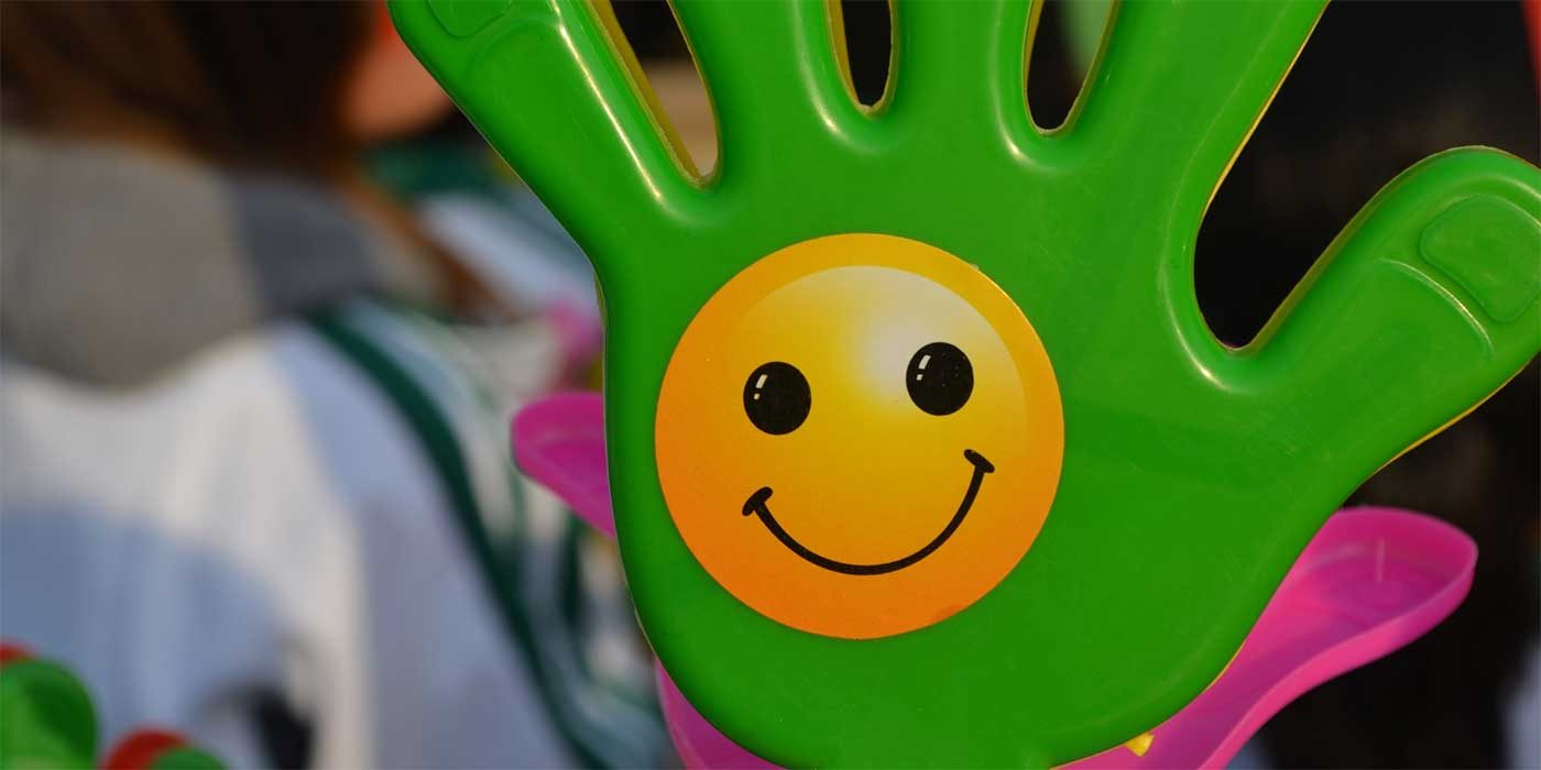 Photo of a toy hand with a happy face sticker