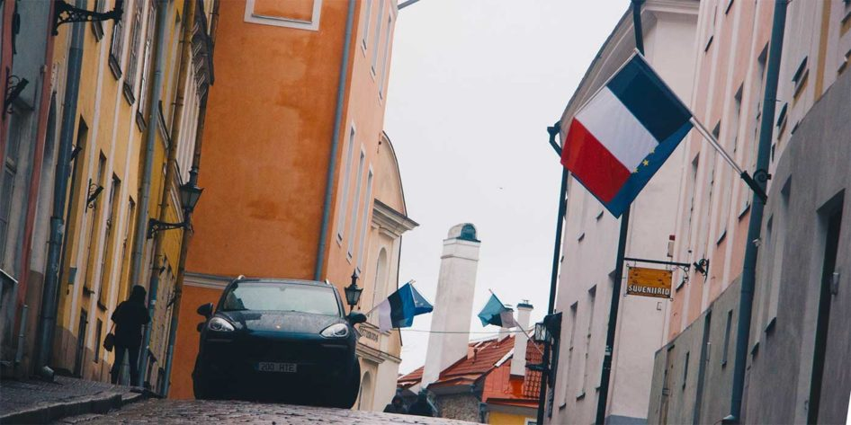 Photo of a French flag on a cobbled street in France