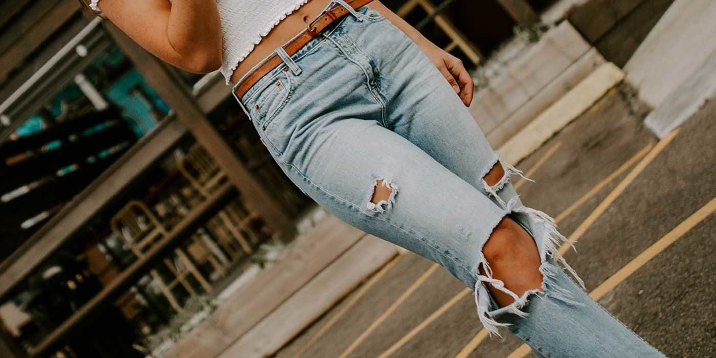 Photo of a woman wearing ripped blue jeans