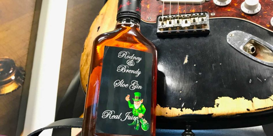 Photo of a bottle of homemade sloe gin and fender stratocaster