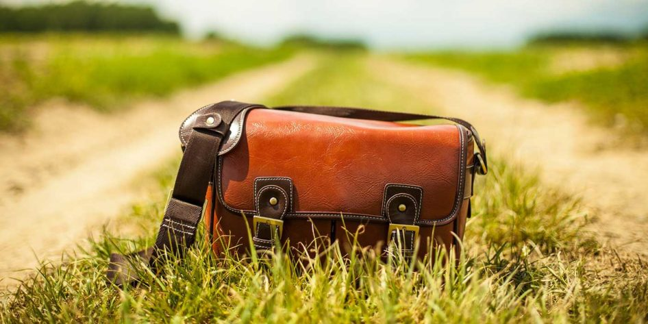 Photo of a leather bag on a grass and dirt lane