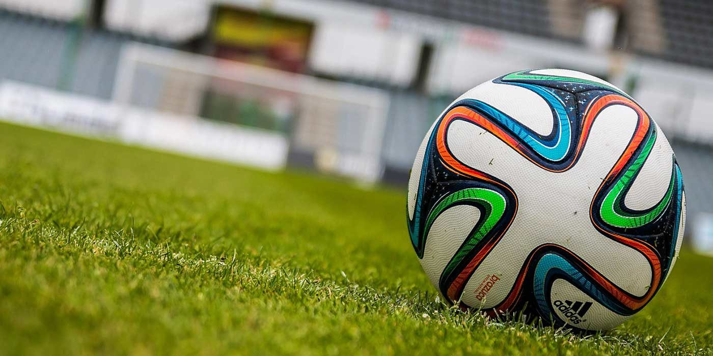 Photo of a soccer football in front of goalposts