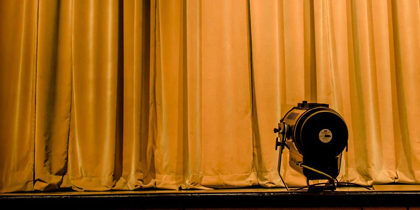 Photo of a stage light in front of a curtain