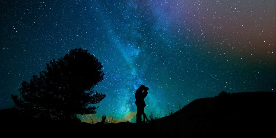 Photo of a couple in front of a night sky with stars