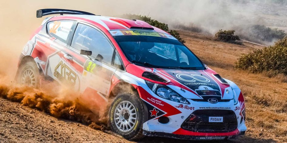 Photo of a rally car going fast on sand