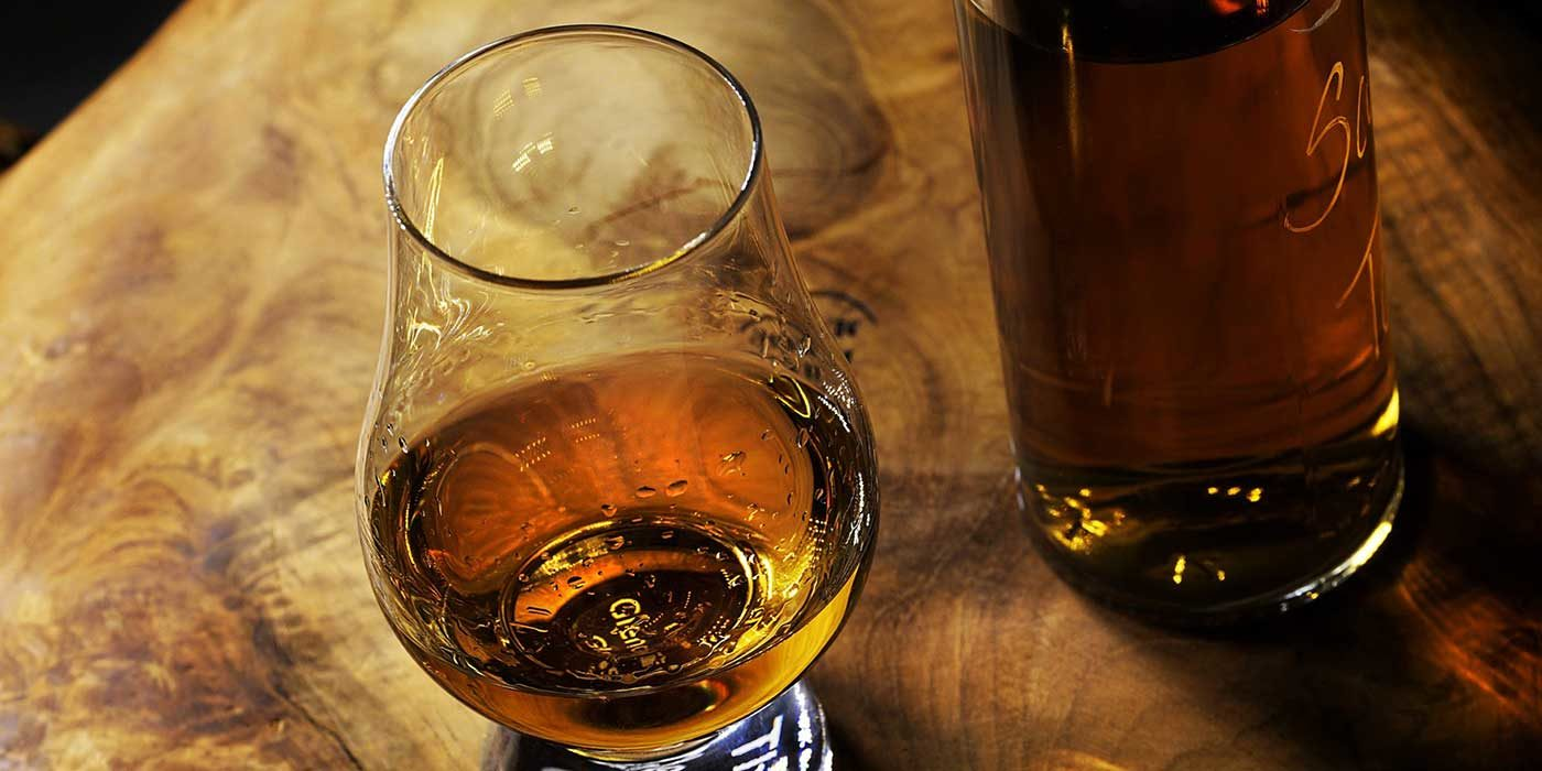 Photo of a whiskey glass and a bottle on a table