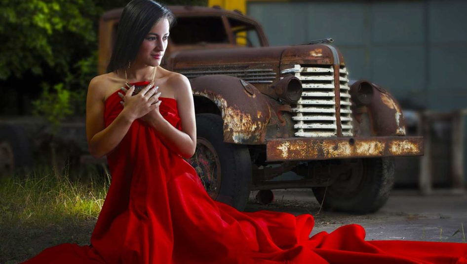 Photo of a lady in a red dress in front of a pickup