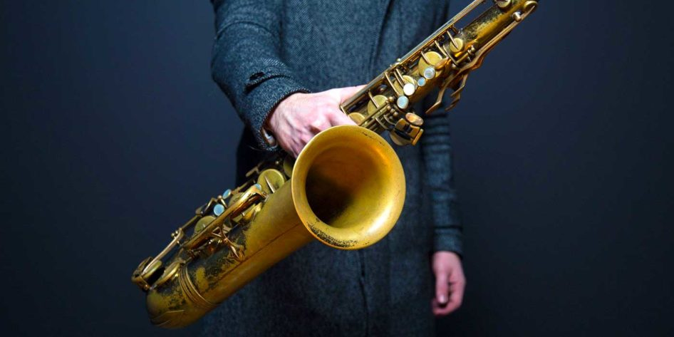 Photo of a musician holding a saxophone