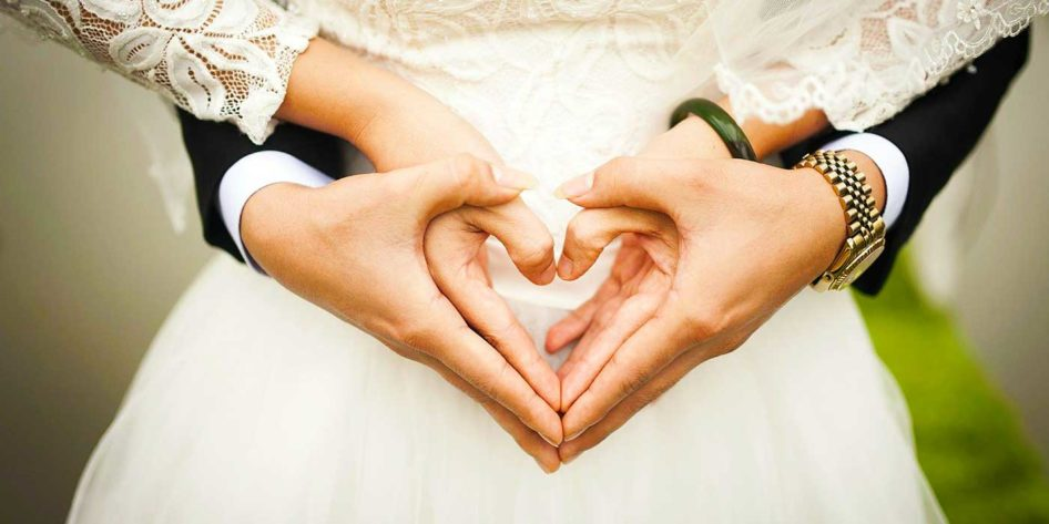 Photo of a bride and groom with their hands shaped as hearts