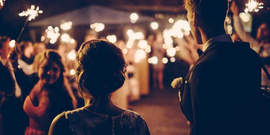 Photo of a bride and groom walking onto the dance floor with guests waving sparklers
